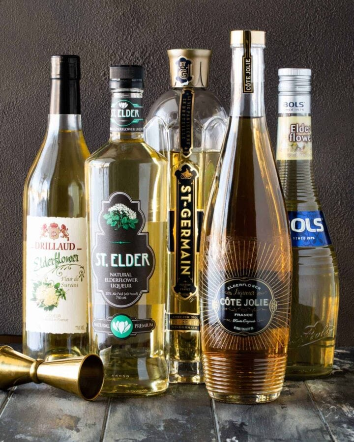 Bottles of different brands of elderflower liqueur with gold jigger.