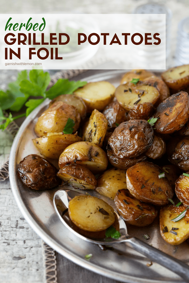 Image of Herbed Grilled Potatoes in Foil on a silver plate with fresh rosemary and fresh parsley.