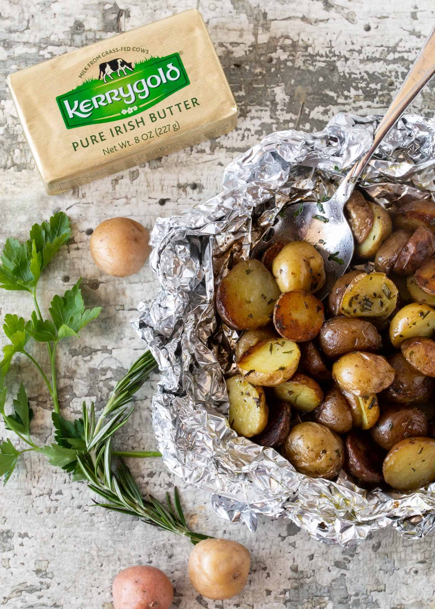 Herbed Grilled Potatoes in Foil packet, garnished with a spoon, fresh rosemary, fresh parsley and next to a block of Kerrygold Salted Butter.