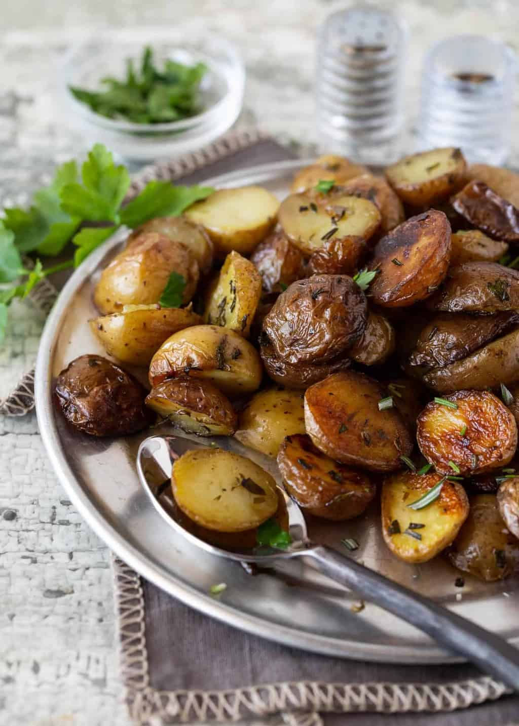 Silver platter full of Herbed Grilled Potatoes in Foil. Garnished with fresh parsley, fresh rosemary, salt and pepper.