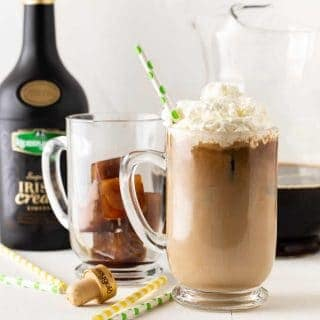 Irish Cream Iced Coffee recipe with whipped cream on top and pitcher of coffee in background.