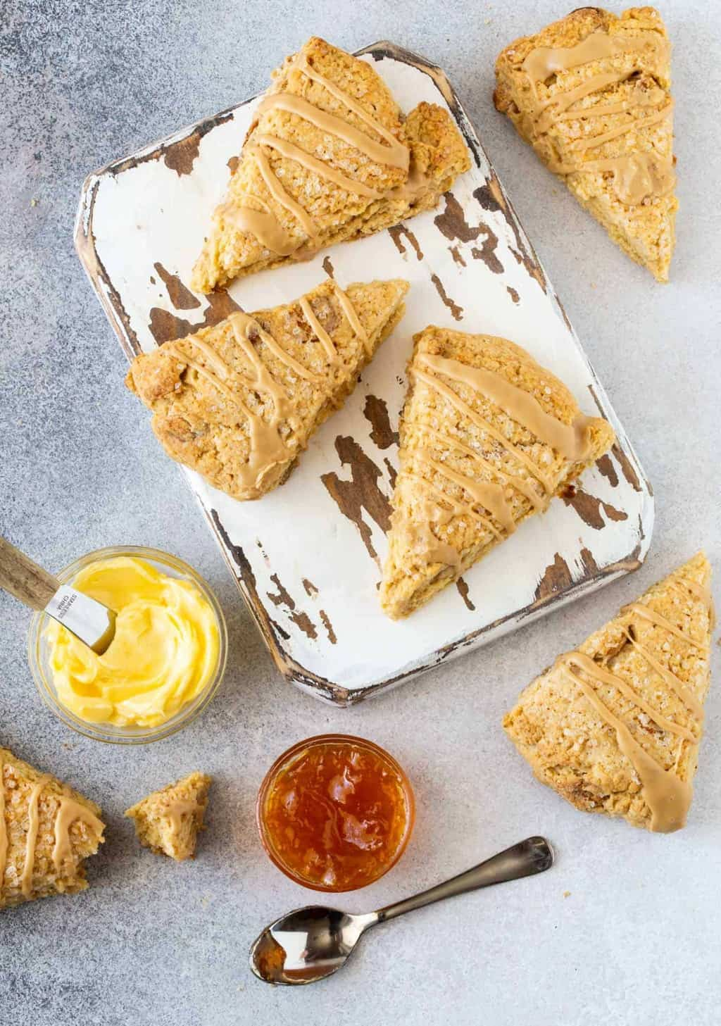 Irish Cream Scones on white wood board, drizzled with Irish Cream Liqueur glaze and garnished with fresh butter and apricot jam.