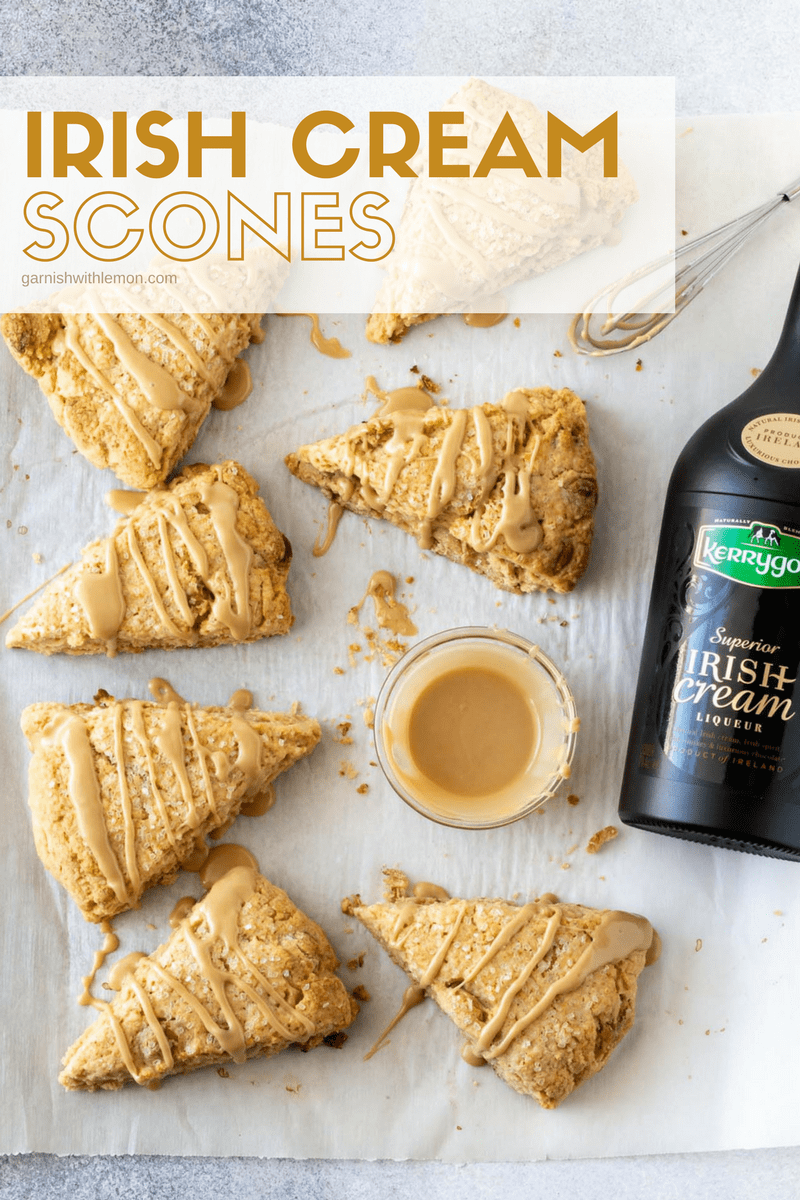 Irish Cream Scones on parchment paper next to bottle of Kerrygold Irish Cream Liqueur and drizzled with irish cream glaze.