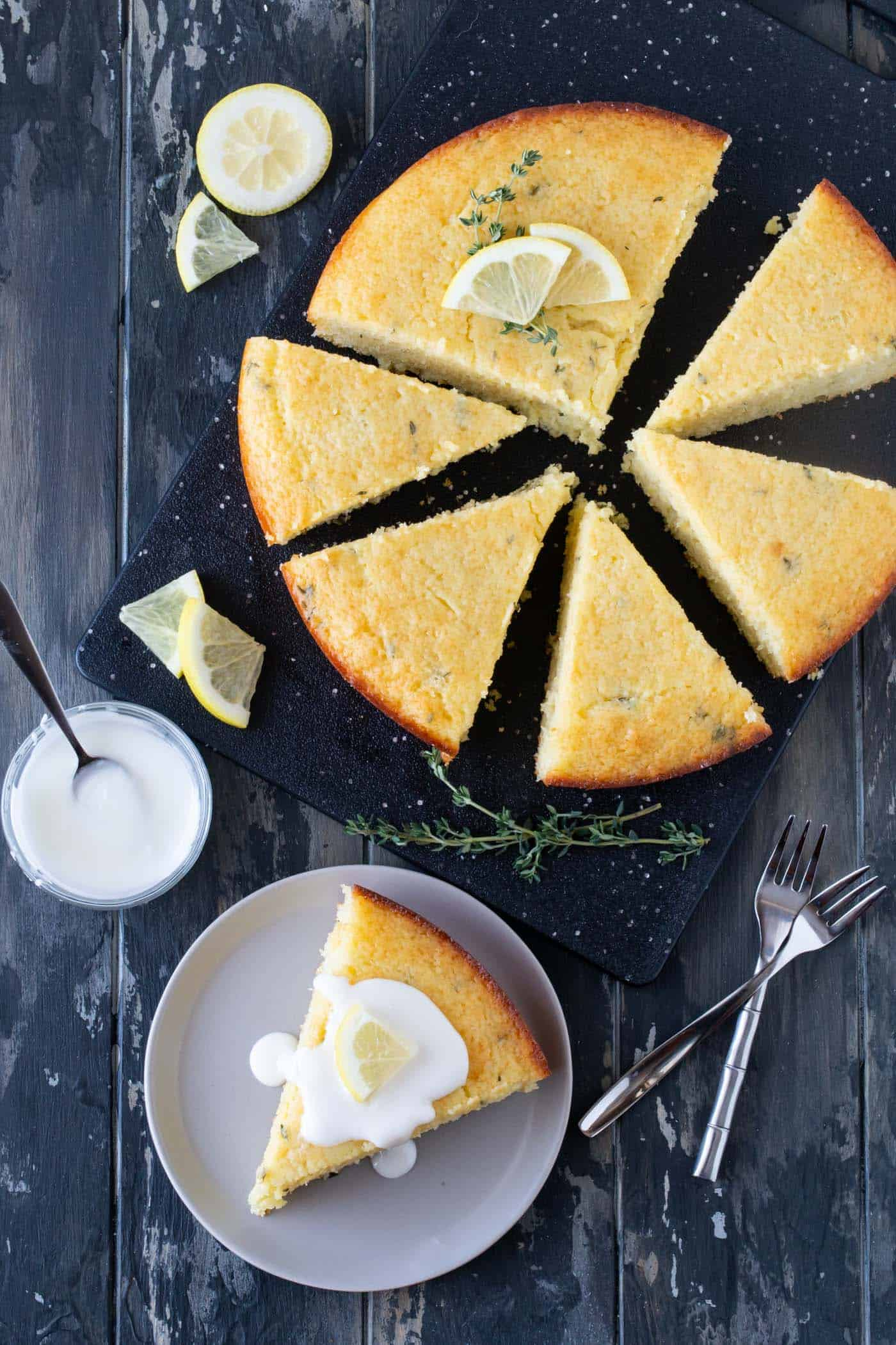 Slices of Lemon Thyme Breakfast Cake on a black cutting board. One slice is garnished with a lemon sugar frosting, fresh thyme and lemon slices.