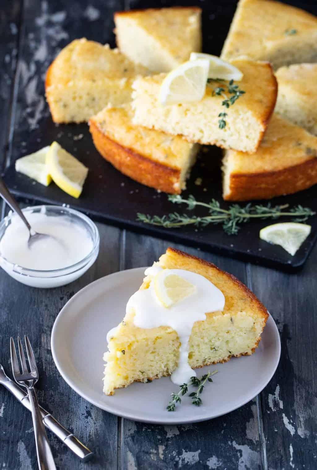 A slice of Lemon cake on a gray plate, garnished with a fresh lemon glaze, a lemon slice and fresh thyme leaves.
