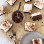 Top down shot of sliced Chocolate Mud Pie Bars recipe with forks for serving and fresh chocolate graham cracker crumbs for garnish.