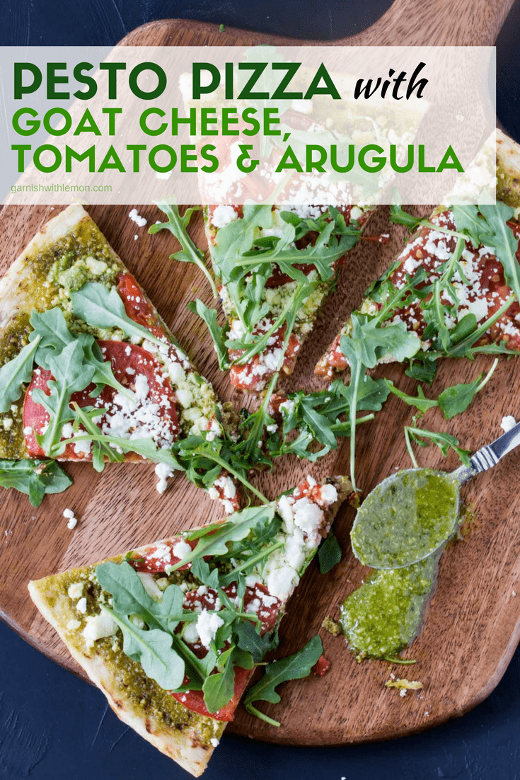 Slices of grilled pesto pizza recipe on a wooden cutting board with goat cheese, arugula, tomatoes and a spoonful of fresh pesto.