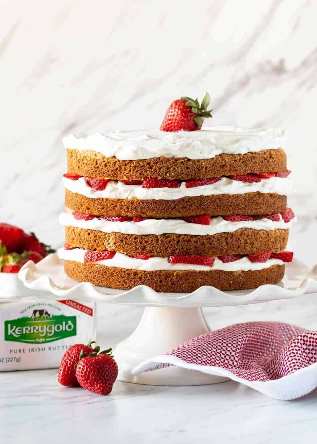 Strawberry Layer Cake filled with fresh whipped cream frosting and fresh strawberries on a white cake stand.