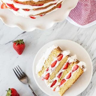 Slice of Strawberry Layer Cake on White plate with cake in background.