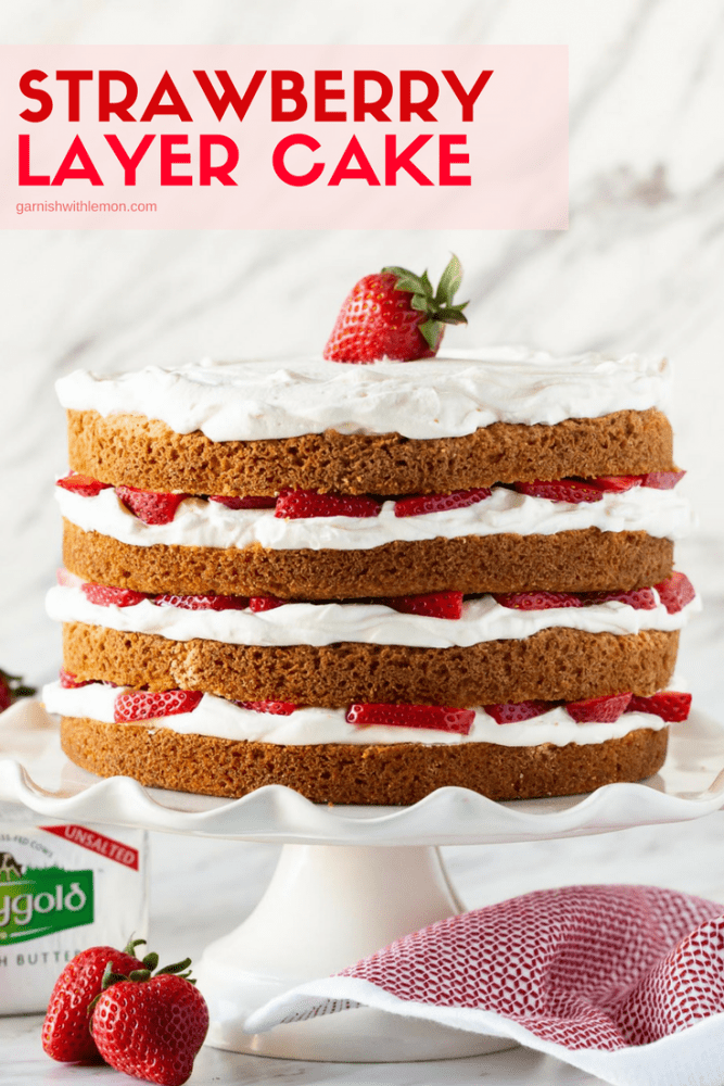 4 Layer Strawberry Lake Cake with fresh whipped cream and strawberries on a white cake stand.