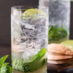 Close up of 2 high ball glasses filled with ice, mint leaves and an elderflower mojito cocktail recipe.
