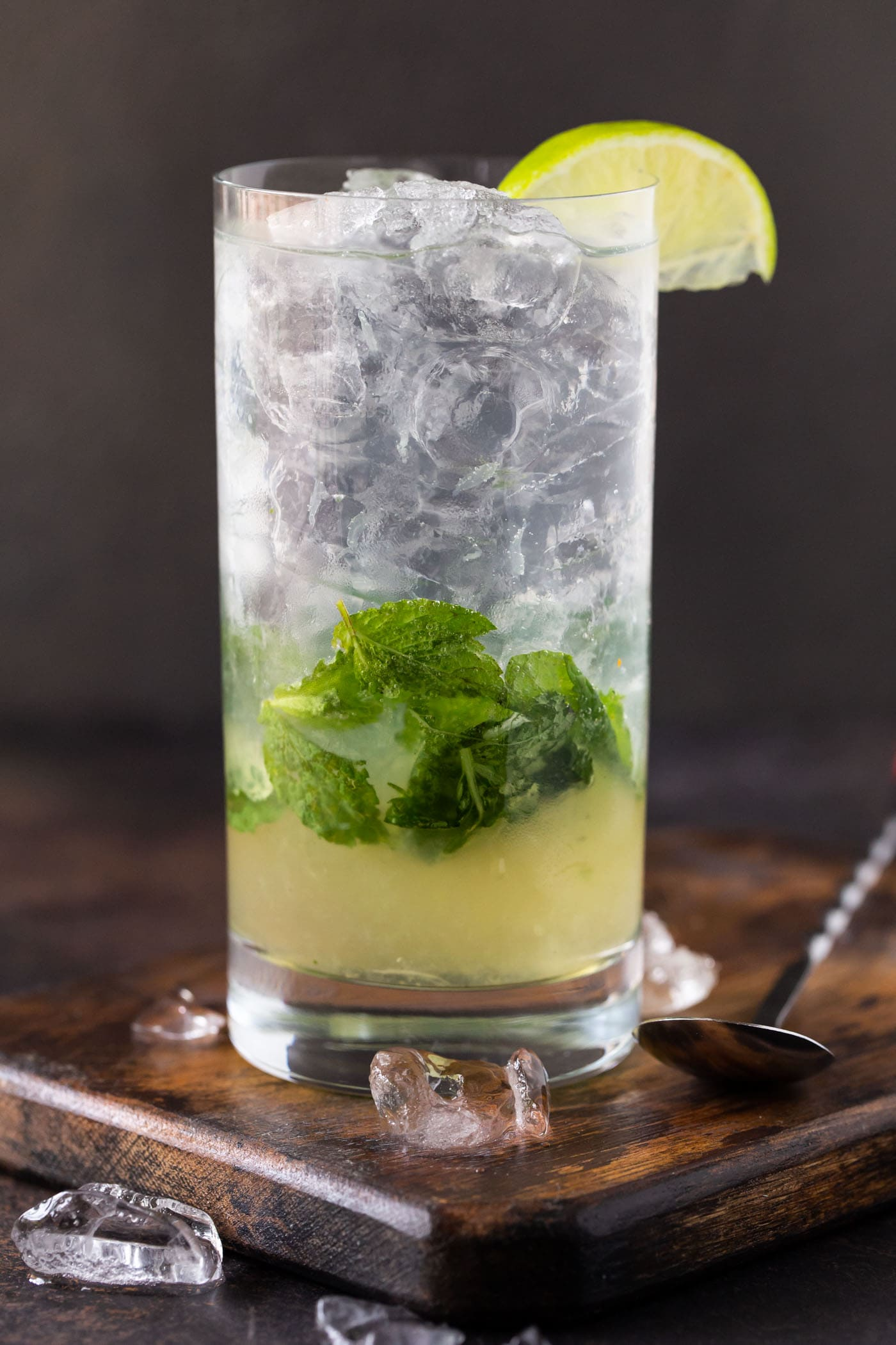 Single high ball glass filled with ice, mint leaves and an elderflower mojito cocktail recipe.