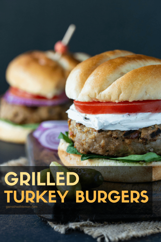 Grilled Turkey Burgers on buns with lettuce, tomato, onion and goat cheese.