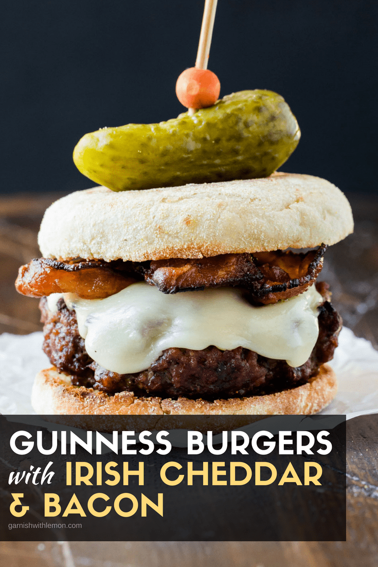 Image of Guinness Burgers with Irish Cheddar and Bacon on a toasted english muffin. Topped with a mini pickle.