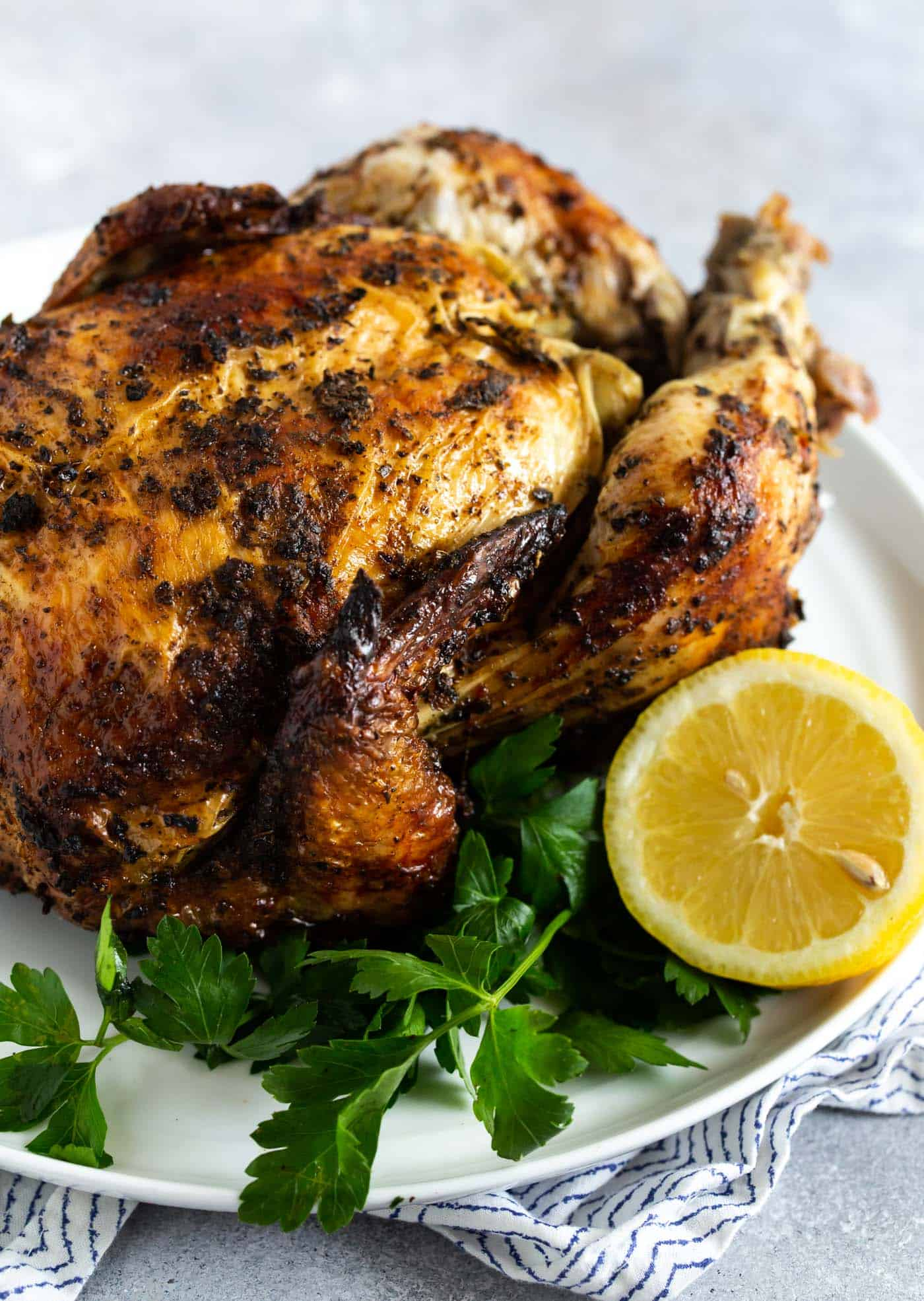 Image of whole roasted chicken on a white plate garnished with parsley and lemon as part of guide for How to Grill a Whole Chicken