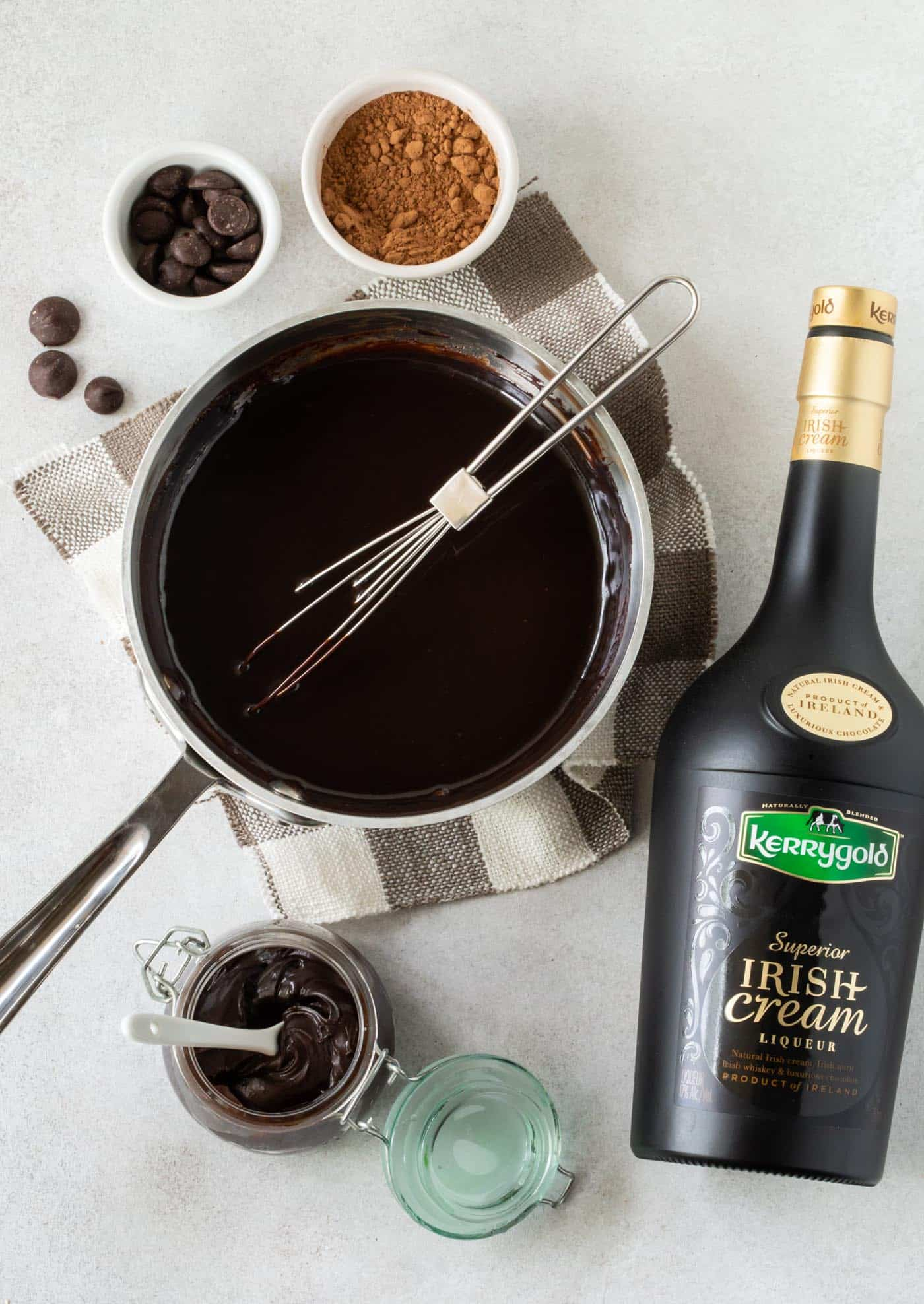 Irish Cream Hot Fudge Sauce Recipe: Sauce pan filled with irish cream hot fudge sauce. Surrounded by fudge sauce ingredients, including cocoa powder, chocolate chips and a bottle of Kerrygold Irish Cream Liqueur.