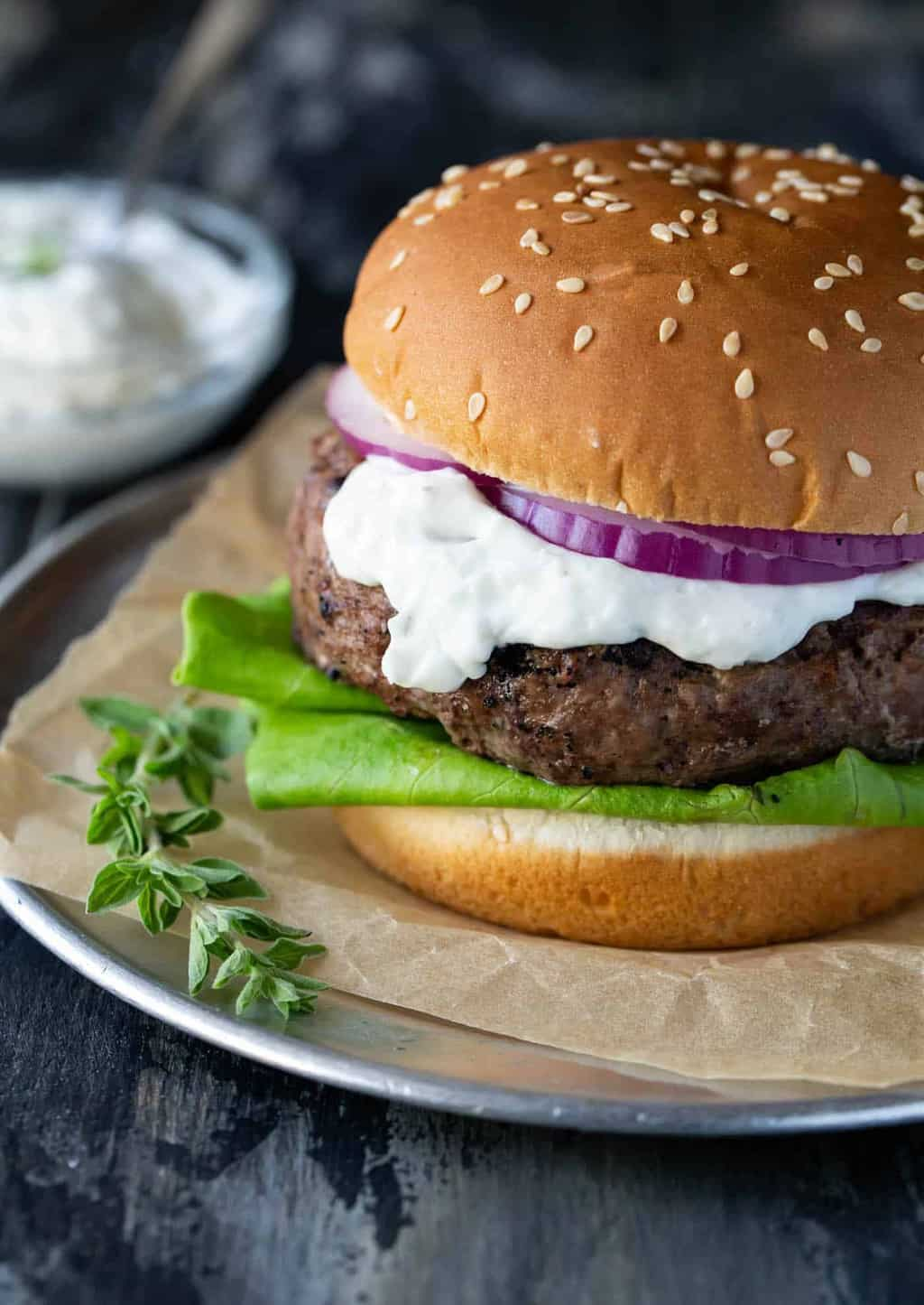 Greek Lamb Burgers with Goat Cheese and Tzatziki Sauce garnished with lettuce, red onion and fresh oregano on a sesame seed bun.