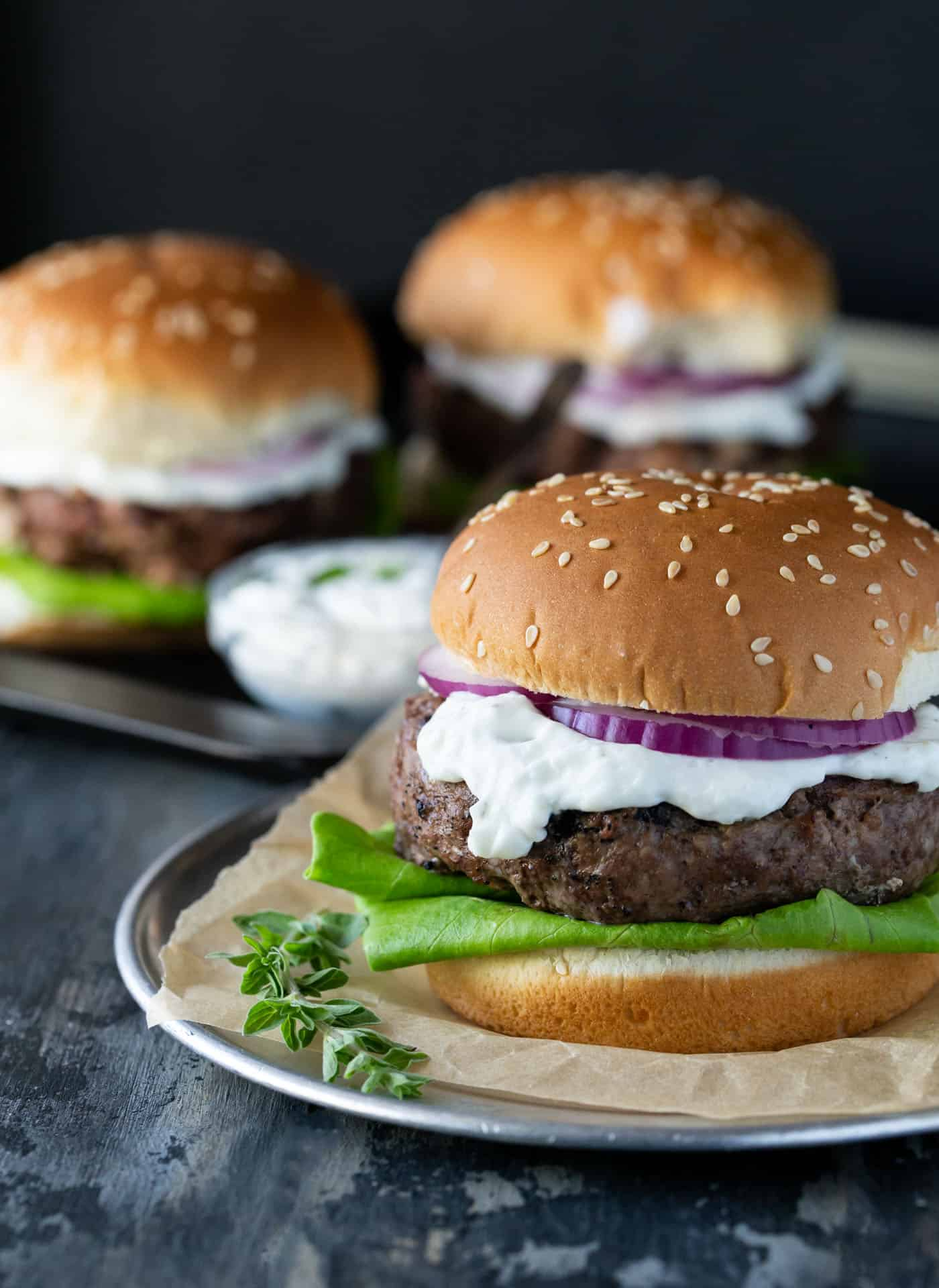 Greek Lam Burger on a sesame seed bun with fresh red onion slices and lettuce for garnish.