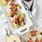 Top down shot of prosciutto wrapped pears with blue cheese garnished with balsamic glaze.
