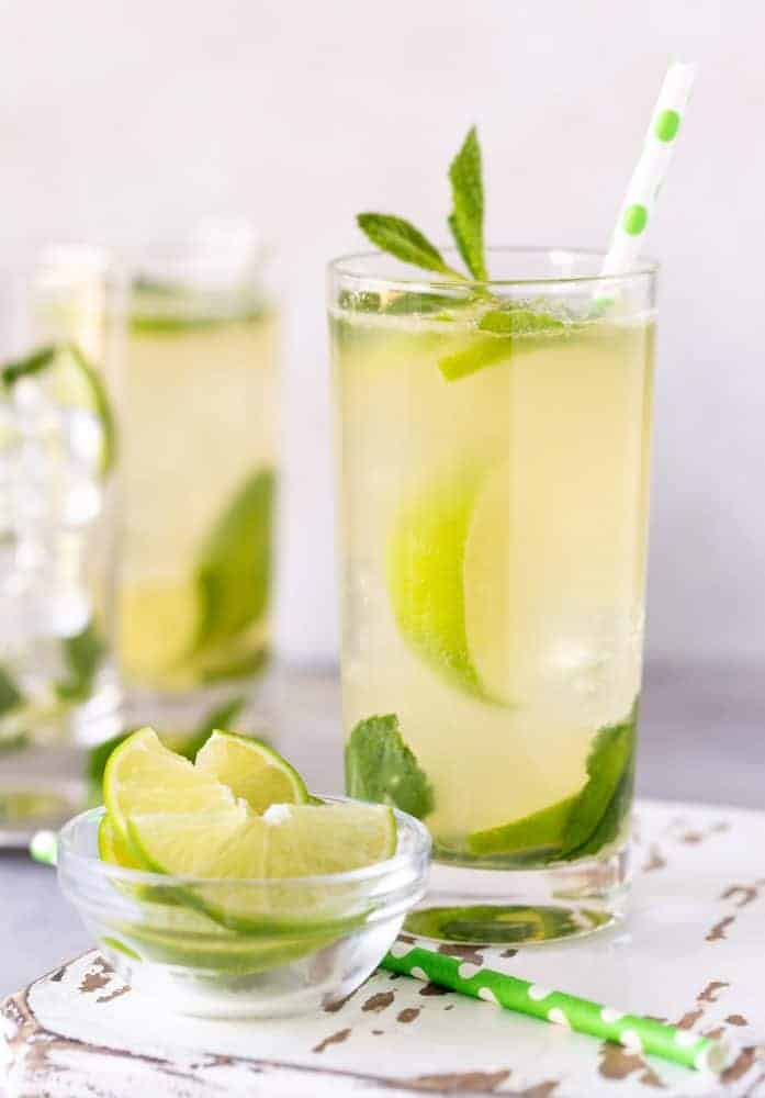 Tequila mojito in high ball glass garnished with fresh lime slices and fresh mint leaves.