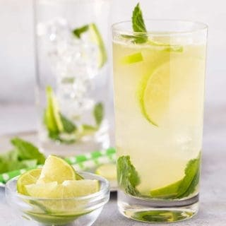 High ball glass filled with Tequila Mojito recipe and garnished with fresh limes slices and mint leaves with green straws.