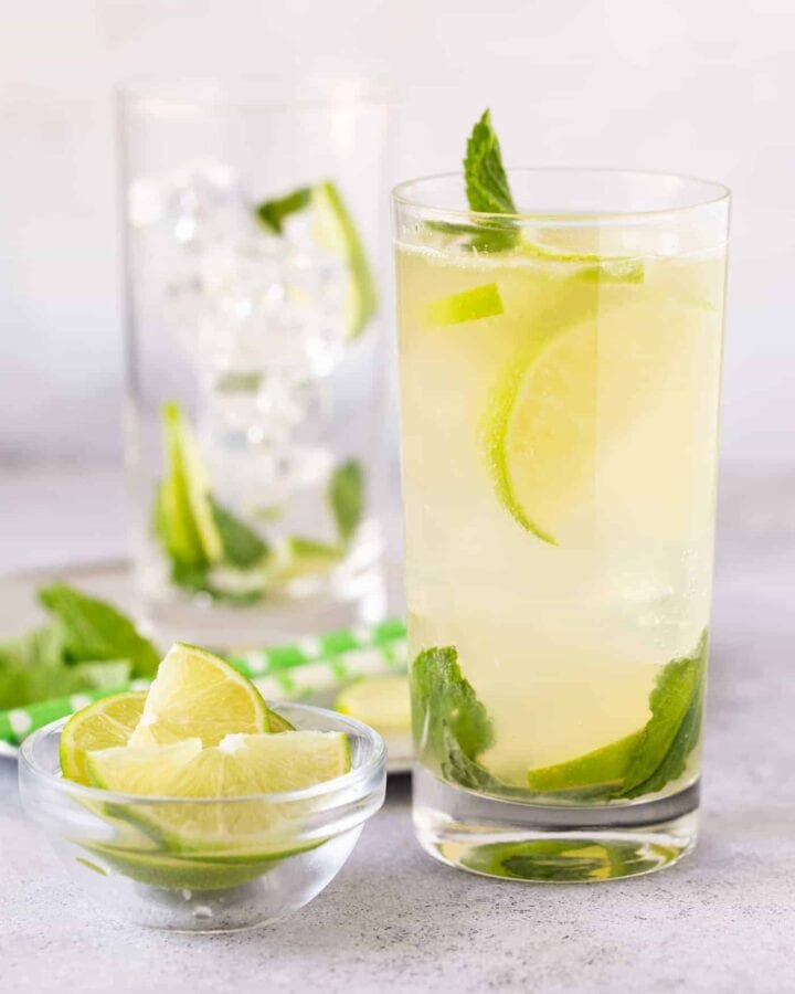 High ball glass filled with  Mojito, with fresh limes slices and mint leaves with green straws.