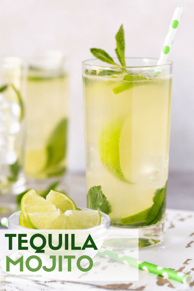 Two tequila mojitos on a light background in high ball glasses filled with ice and garnished with fresh mint leaves and limes.