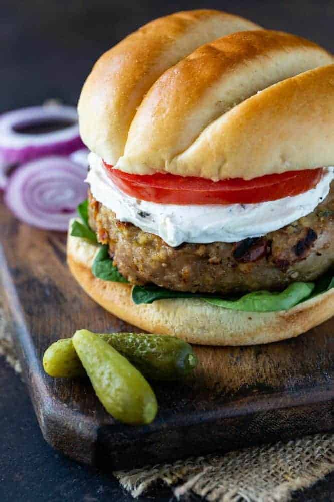 Grilled Turkey Burgers with Sun-dried Tomatoes and Goat Cheese garnished with lettuce, tomato and pickles.
