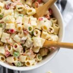 White bowl filled with creamy, Classic Macaroni Salad recipe on a white countertop with two wooden spoons.