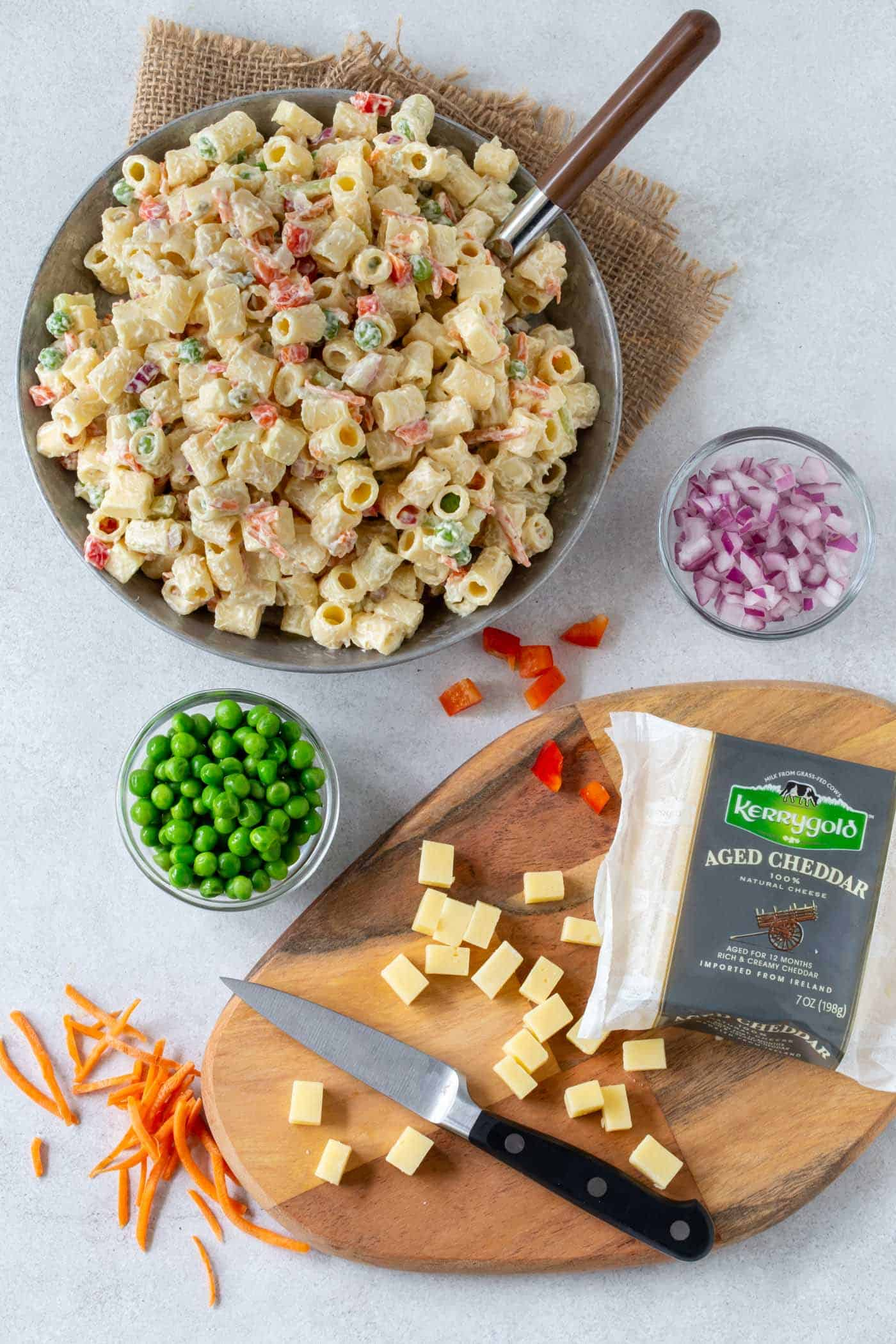 Grey bowl filled with creamy, Classic Macaroni Salad recipe. Surrounded by ingredients like chopped red onion, bell pepper, carrots and diced Kerrygold Aged Cheddar Cheese.