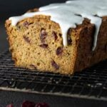 Loaf of Cranberry Zucchini Bread on a cooling rack with a drizzle of vanilla bean glaze.