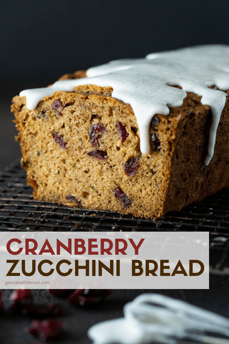Sliced loaf of Cranberry Zucchini Bread on a dark cooling rack drizzled with rich vanilla bean glaze.