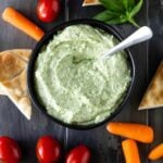 pesto dip in a dark bowl with carrot sticks, pita chips and grape tomatoes for dipping.