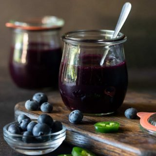 Two glass jars filled with Easy Blueberry Jalapeno freezer jam. Garnished with a spoon, extra blueberries and jalapeno pepper slices on a dark wood cutting board.