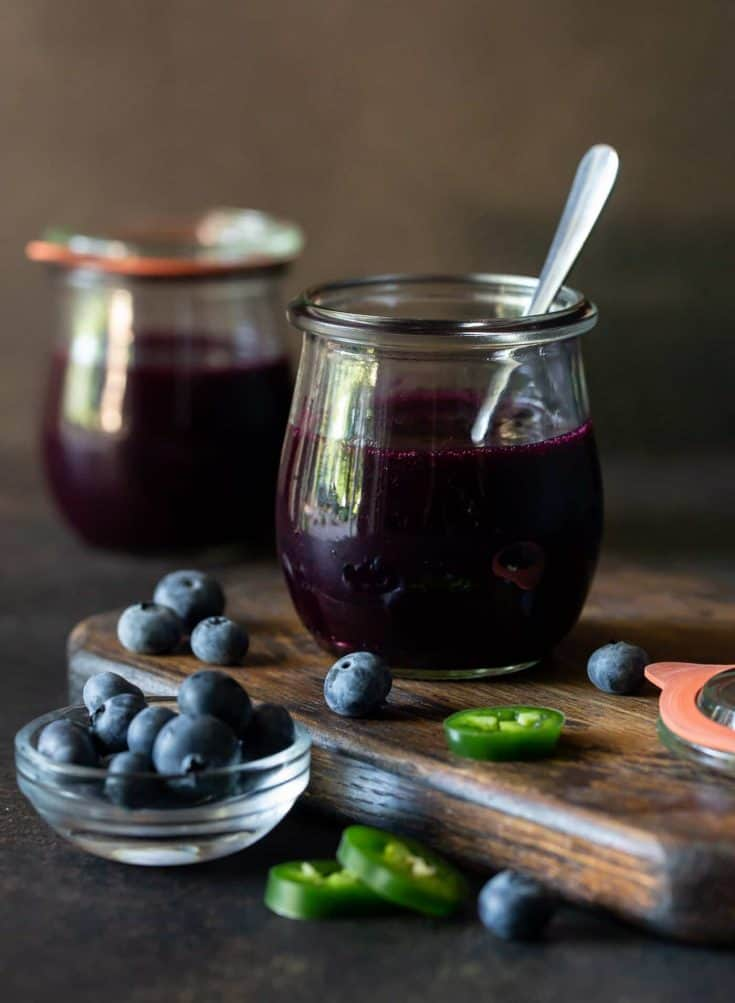 Two glass jars filled with Easy Blueberry Jalapeno freezer jam.