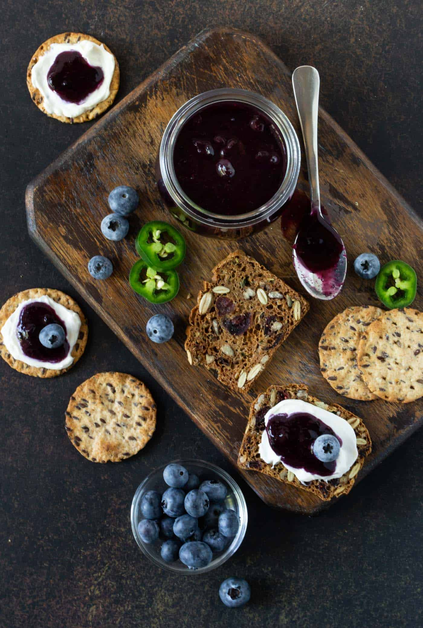 Crackers spread with cream cheese and Easy Blueberry Jalapeno Freezer Jam on a dark wood cutting board. Surrounded by jar of jam, spoon and extra fresh blueberries and jalapeno slices.