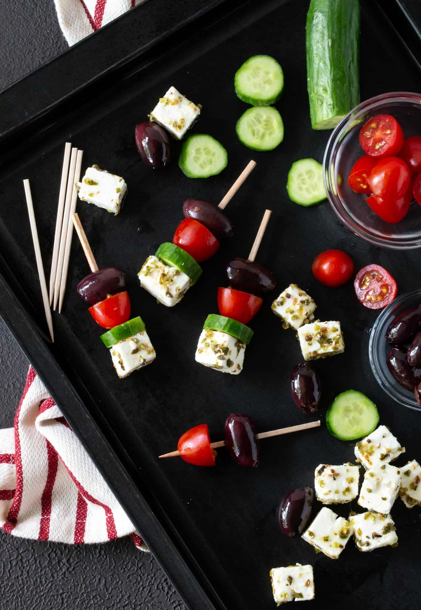 dark sheet pan filled with ingredients for Greek Salad Skewers including kalamata olives, feta cheese, grape tomatoes and cucumber chunks.