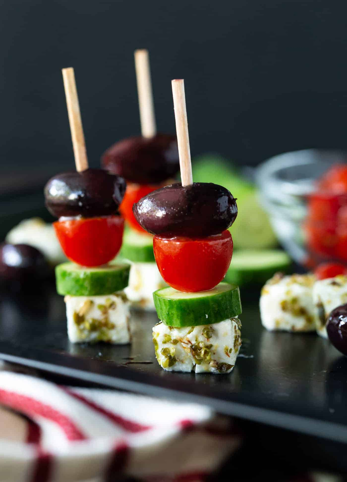 Three Greek Salad Skewers on dark platter with cubes of feta cheese, chunks of cucumber, kalamata olives and sliced tomatoes