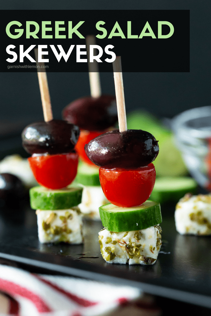 three Greek Salad Skewers made with marinated feta cheese, cucumber, tomatoes and kalamata olives.