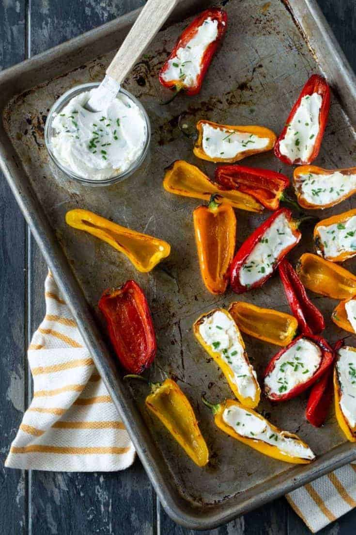 Top down image of grilled peppers with goat cheese recipe on sheet pan with fresh herbs for garnish.