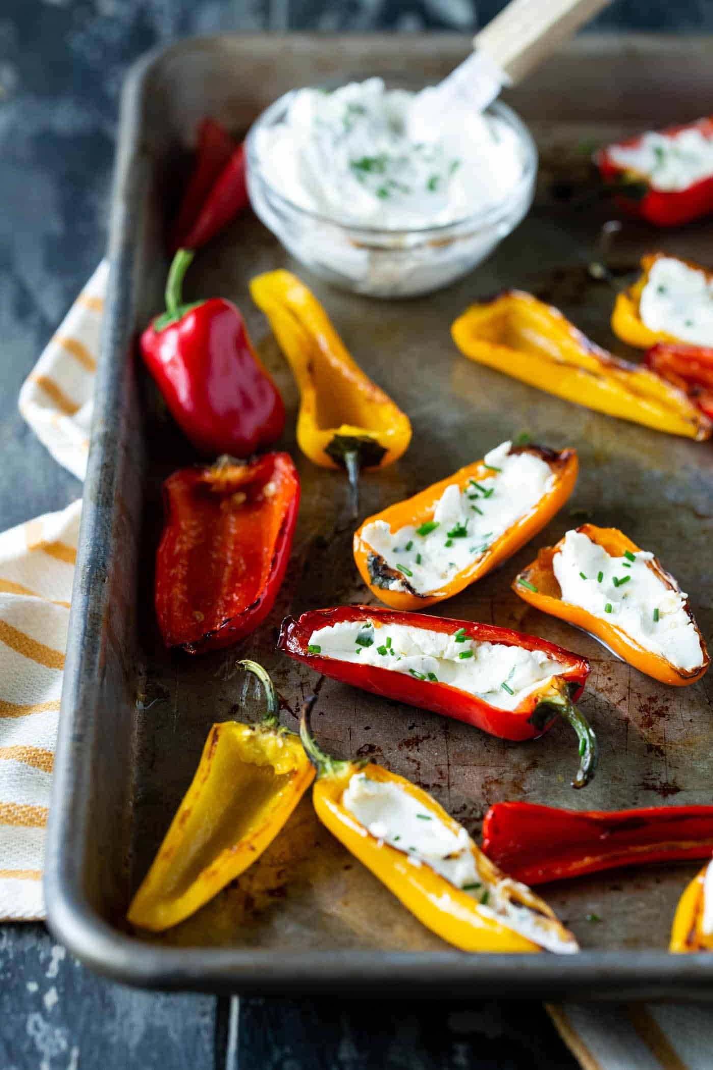 grilled peppers with goat cheese on sheet pan with fresh herbs for garnish and bowl of goat cheese spread on side.