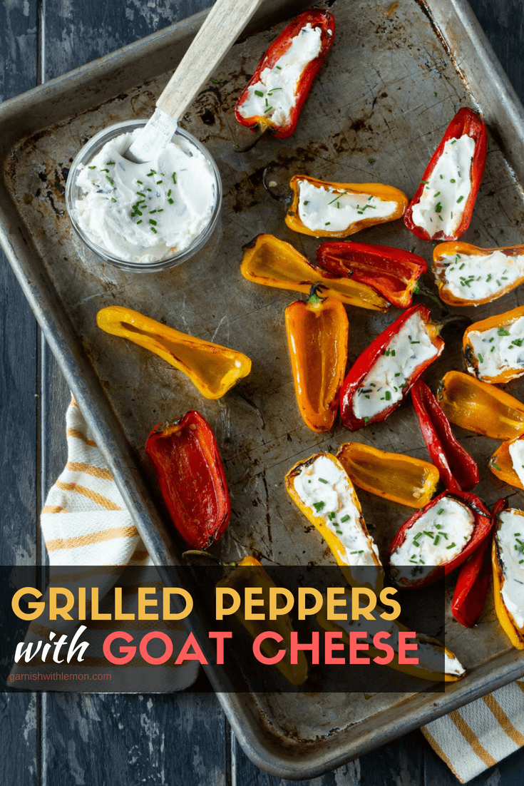 Grilled Peppers with Goat Cheese on sheet pan with dark background and fresh herbs for garnish.