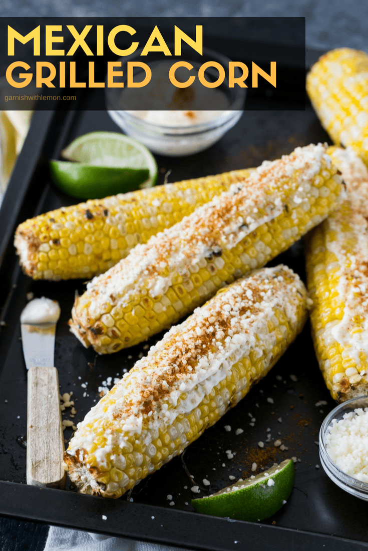 Sheet pan filled with Mexican Grilled Corn and garnished with lime wedges, cotija cheese and mayonnaise.
