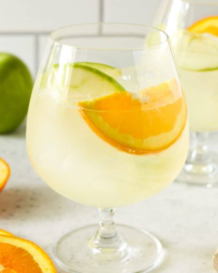 glass filled with lemonade and fruit slices.