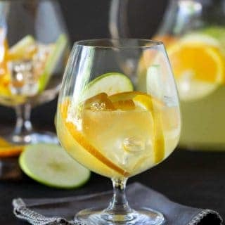 Close up shot of glass of Sangria Lemonade garnished with fresh apples, orange and lemon slices.