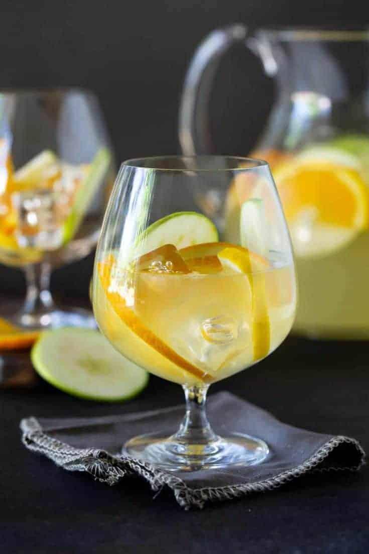 Close up shot of glass of Sangria Lemonade garnished with fresh apples, orange and lemon slices.