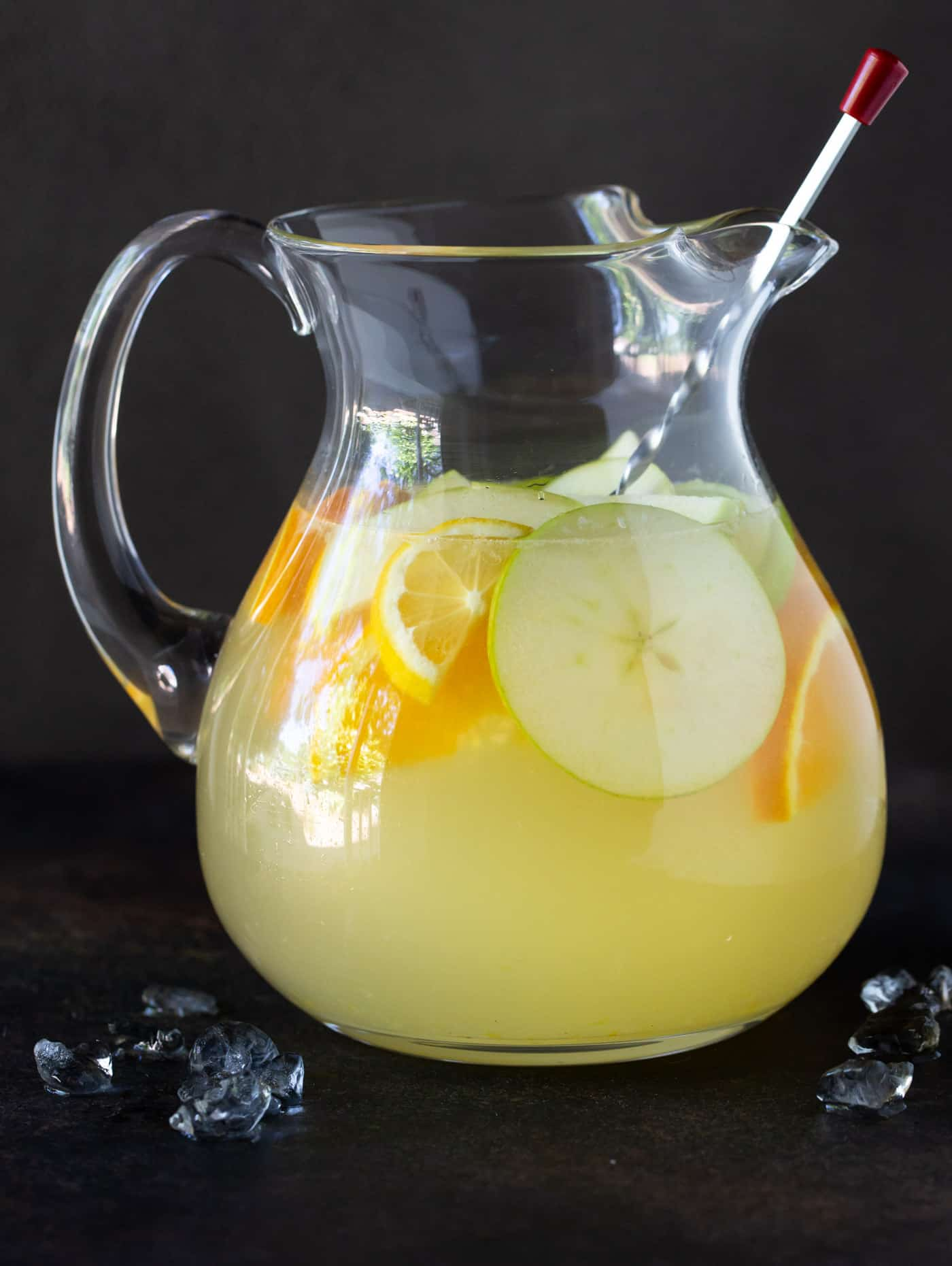 Pitcher of Sangria Lemonade on a dark background with ice scattered in foreground.