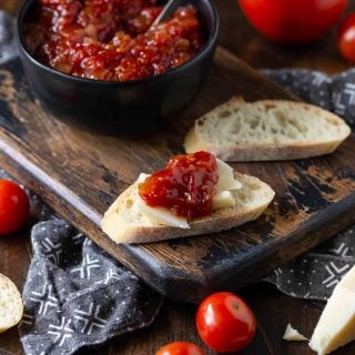 Sweet and Tangy Tomato Jam recipe spread on a baguette slice with fresh cheese. Bowl of jam in background along with additional slices of cheese and baguette.