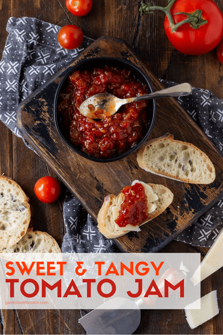 slices of baguette topped with Sweet and Tangy Tomato Jam recipe along with cheese and fresh tomatoes on wood cutting board.