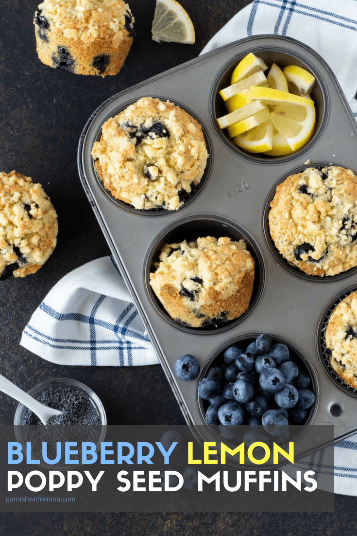 Muffin tins filled with Blueberry Lemon Poppy Seed Muffins. Garnished with fresh lemon slices, fresh blueberries and a bowl of poppy seeds.